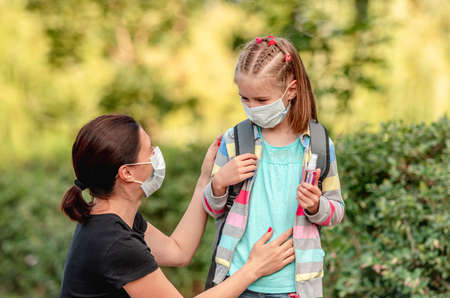 Foto de Mother putting mask on daughter before school - Imagen libre de derechos