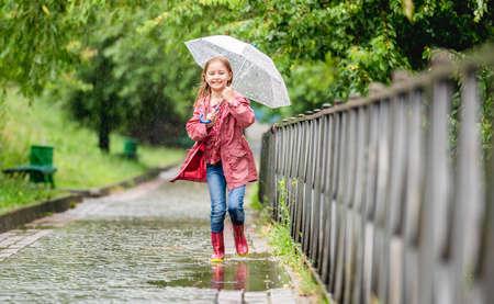 Photo pour Little girl running through puddles - image libre de droit
