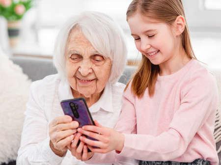 Photo pour Grandmother with grandaughter using smartphone - image libre de droit