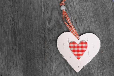 Wooden white and red heart on a black and white old wooden background.