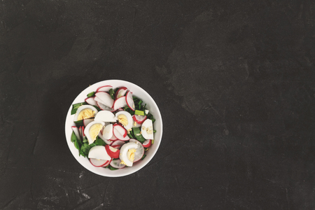 Vegetable vegan salad of ramson, radish, green onions and boiled eggs in a white plate on a dark concrete background, in retro treatment. Close-up, top view, flatlay. The concept of healthy nutrition