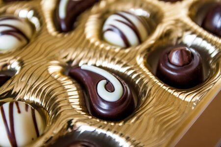 Photo pour Chocolate candies of different shapes in a gold box, a perspective view and blur. - image libre de droit
