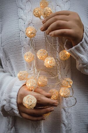 lights in the palms. Female hands hold a garland with wicker round balls. Girl in a white sweater with Christmas lights in her hands, warm New Year mood, soft focus.