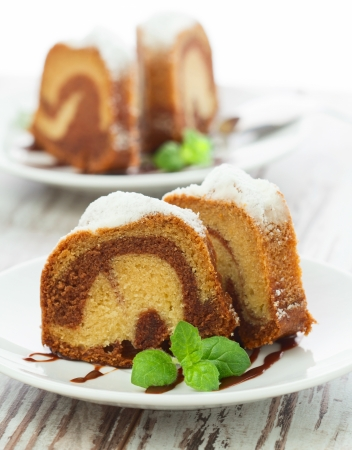 Photo pour Vanilla and chocolate cake sliced with mint laves  on wooden table - image libre de droit