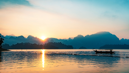 Photo pour silhouette image of a  boat sailing in a dam in southern of Thailand in the morning. - image libre de droit