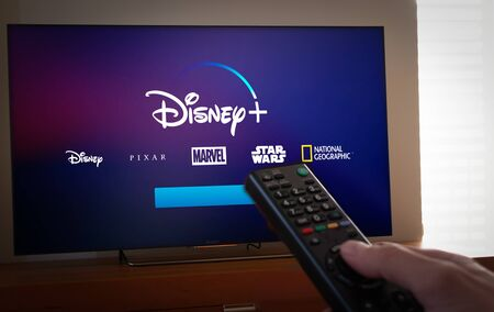 Photo pour Barcelona, Spain. January 2019: Man holds a remote control With Netflix, HBO and the new Disney  logos on TV screen - image libre de droit