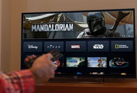 Photo pour Barcelona, Spain. November 2019: Man holds a remote control with the new Disney plus screen on TV - image libre de droit