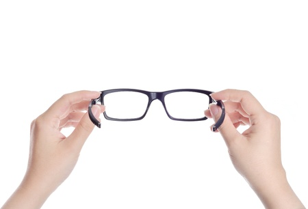 woman hands holding black eyeglasses on white background