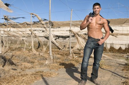 muscled man with jeans laughing in desolated landscape