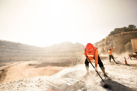 Foto de Miners working with mining tool in dusty and baking hot, mining and summer hot sun in the backgrounds. Hard work concept. Noise, Grain. - Imagen libre de derechos