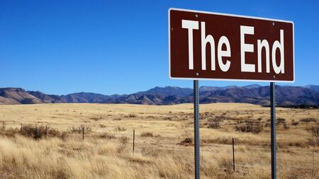 The End road sign with blue sky and wilderness