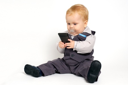 blond baby in suit texting with mobile phone