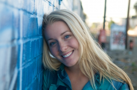 A smiling blond girl and a graffiti wall