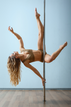 Photo pour Young slim sexy blond woman in beige dress pole dancing against the background of the wall. - image libre de droit