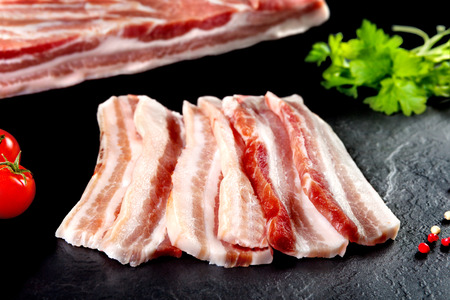 Fresh and raw meat. Still life of bacon BBQ steaks. black slate background