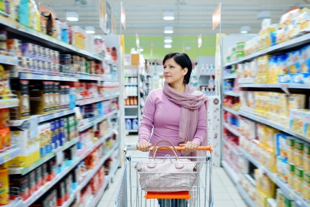 pretty smiling woman pushing shopping cart looking at goods in supermarket
