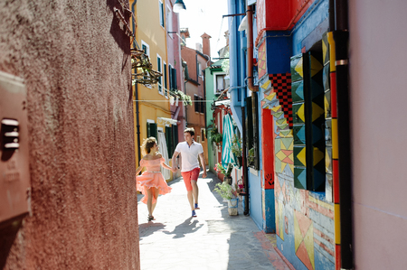 Travel couple walking down the alleys of Burano island, Venice, Italy, Europe