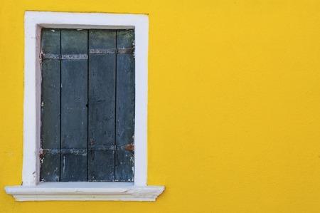 Yellow wall and wooden window, Burano island, Venice, Italy