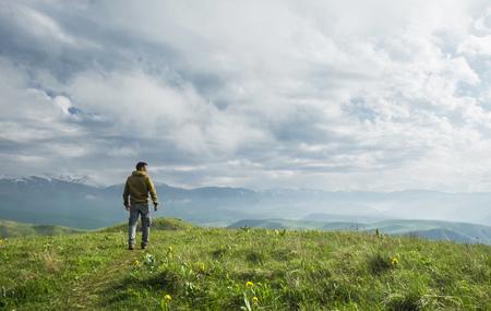 Foto de Beautiful landscape, man standing on the hill in front of mountains - Imagen libre de derechos