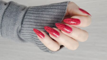 Foto de Female hand with long nails and a bottle of bright red nail polish - Imagen libre de derechos