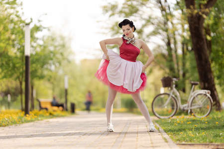 Photo pour A girl in a pink dress and hairstyle in the style of the 40-50s dances and poses in the park on a sunny day. Retro style photo. - image libre de droit