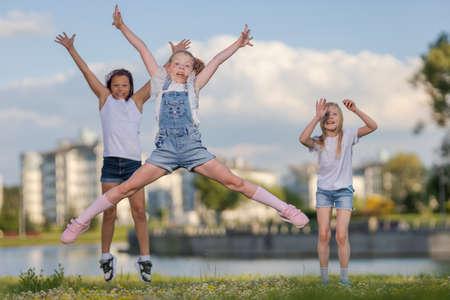 Photo pour Children girls friends run, jump and pose near a lake in a city park on a sunny day - image libre de droit
