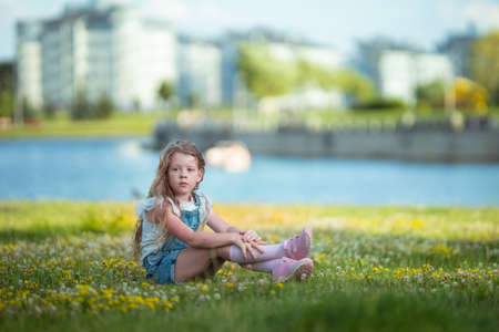 Photo for Blonde girl dancing, jumping, doing acrobatics and posing, in a city park on green grass near a lake on a sunny day - Royalty Free Image