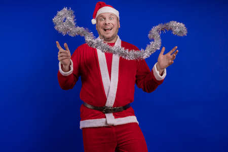 Male actor in a suit and hat of Santa Claus with a red tinsel garland dancing and posing on a blue background
