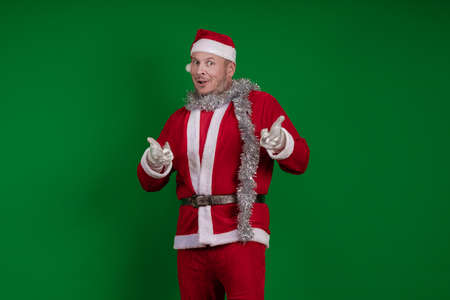 Male actor in a costume of Santa Claus gesturing and posing on a green chroma background