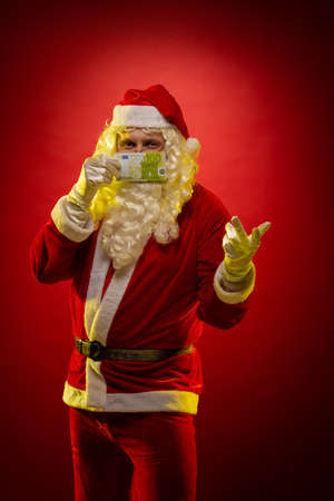 Male actor in a costume of Santa Claus holds in his hands banknotes, money and posing on a dark red background