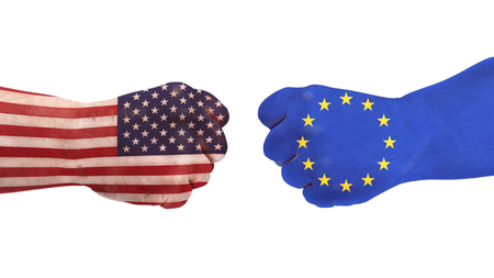 Two fists are painted with flags of USA and Europe. They stand symbolically opposite to the respective states. A symbolic picture of a current economic topic.