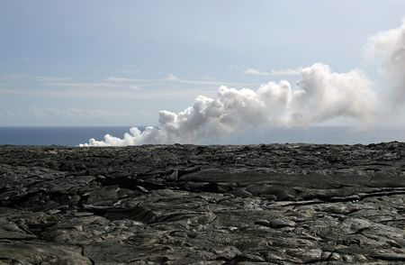 Hardened lava fields of the Kilauea Volcano with steam billowing from hot lava entering the Pacific Ocean. Exploring the lava is a popular tourist activity on the Big Island of Hawaii.