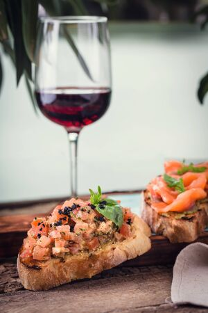 Photo for different bruschetta on a wooden board with a glass of wine - Royalty Free Image