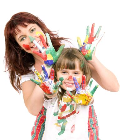 Mother together with a daughter is shown with palms soiled with a paint of different colors, smile