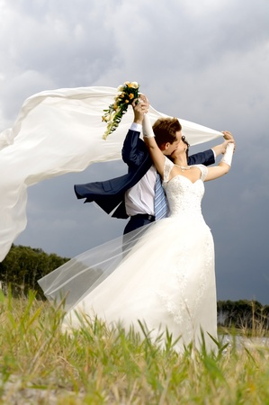 the beautiful  happy married  couple  on nature, puff wind, hot kissの写真素材