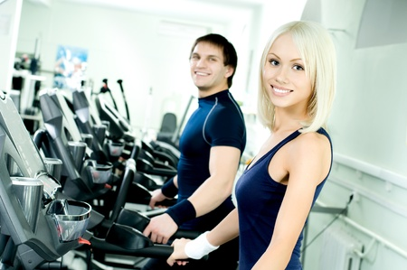 happy cutie athletic girl and guy,  execute exercise on  running track  and smile, in  sport-hall