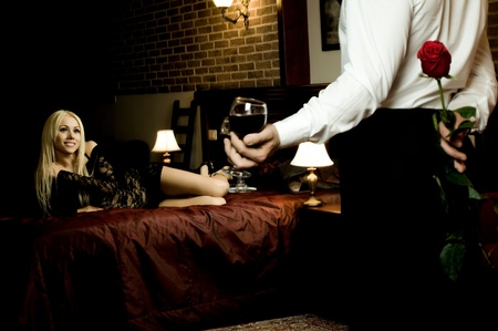 romantic evening date in hotel room, guy with red rose ,  girl on bed smile