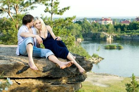 Foto de romantic  date on nature, happy couple sit aloft on rock  with beautiful view - Imagen libre de derechos