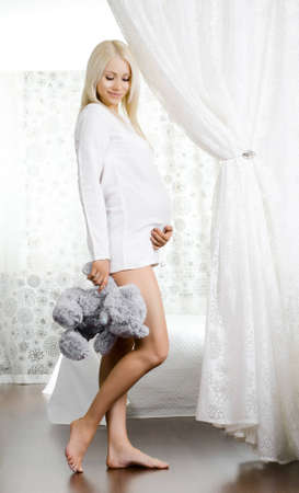 young pregnant woman with toy, in  light bedroom