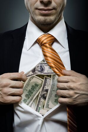 venality businessman or banker  in black costume throw open one's shirt packed heap dollars