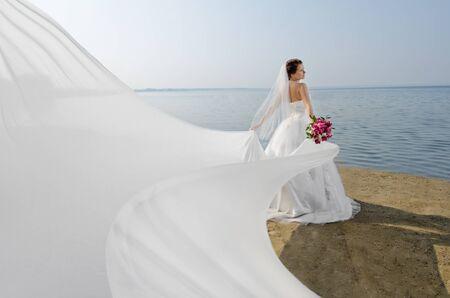 Foto de beautiful fiancee in white wedding dress and big long white train, stand on shore sea - Imagen libre de derechos