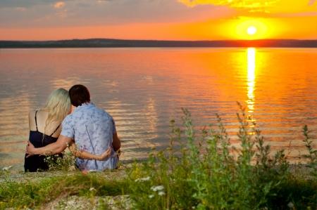 Foto de romantic evening date on nature, couple on beautiful sunset on  lake - Imagen libre de derechos