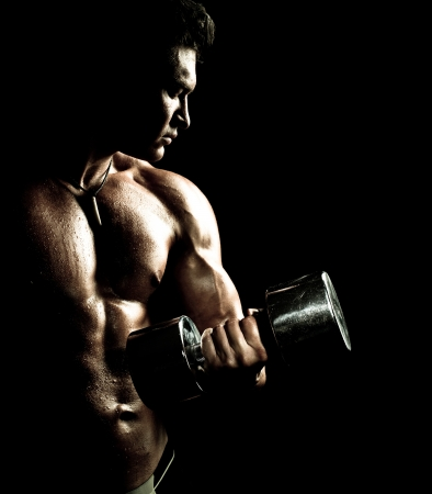 very power athletic guy ,  execute exercise with  dumbbells, on bkack background
