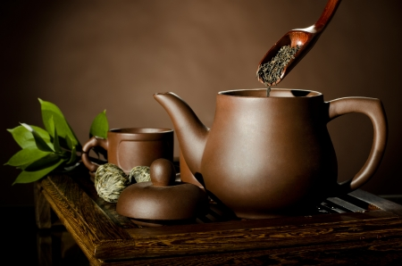 horizontal picture, tea pour in clay teapot,   on brown background,  tea ceremony