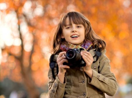 horizontal photo, happy beautiful little girl with photocamera, autumnal portrait