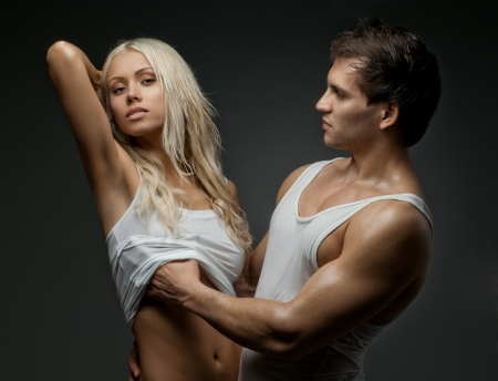 muscular handsome sexy guy with pretty woman, on dark background