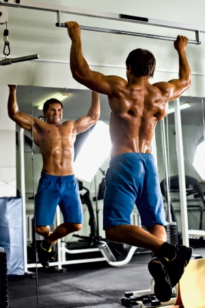 very power athletic guy ,  execute exercise tightening  on horizontal bar, in  sport-hall, glamour light