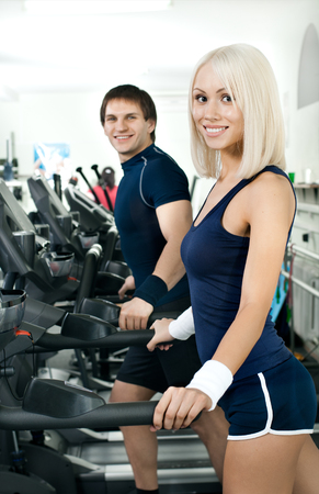happy athletic girl and guy,  execute exercise on  running track  and smile, in  sport-hall