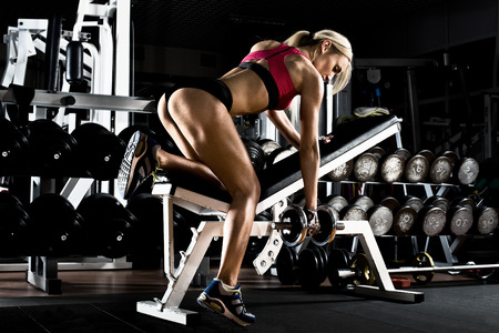 fitness girl  execute exercise with  dumbbells, on broadest muscle of back