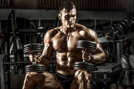 very power athletic guy bodybuilder , sit with  dumbbells, in dark gym